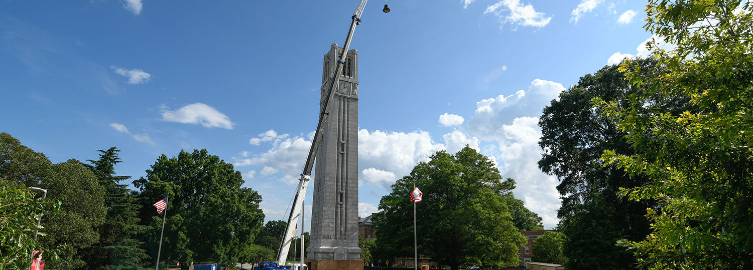 crane holding bell to be installed in the top of the belltower