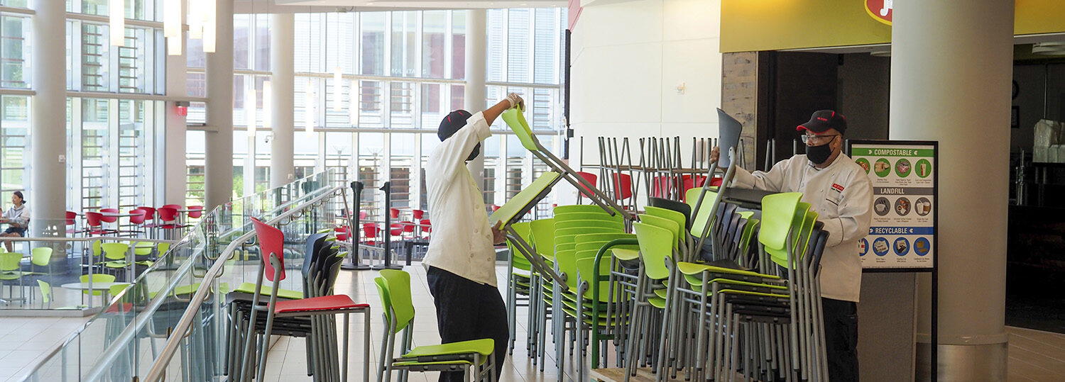 Workers remove green chairs from Talley Student Union to limit seating capacity during the COVID-19 pandemic.
